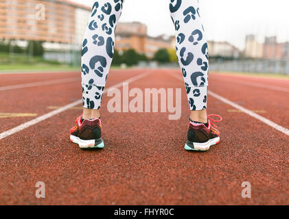 Athlete woman standing on a running track - Stock Photo