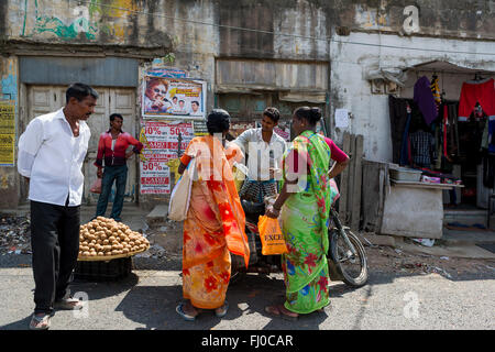 A group of Indian people standing and talking around a motorcycle in front of shops along the roadside near to Chennai - Stock Photo