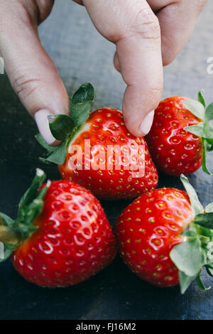 Fingers taking a strawberry - Stock Photo