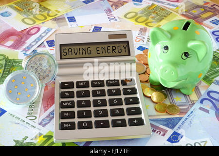 Pocket calculator with the words Saving Power, two LED lamps and a green piggy bank on a background made of Euro - Stock Photo