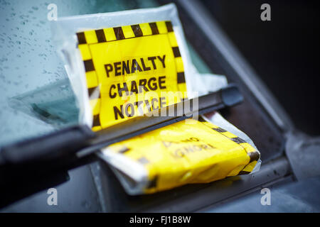 Parking ticket penalty charge notice on the windscreen under a wiper blade - Stock Photo