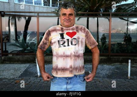 Man with 'I LOVE RIO' t shirt on Ipanema beach, Rio de Janeiro, Brazil - Stock Photo