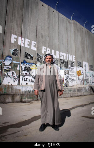 A Palestinian man stands at Bethlehem checkpoint in front of separation wall - Stock Photo