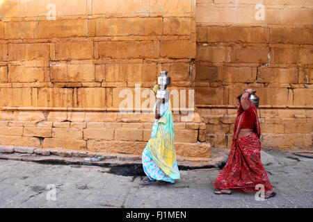 two women are carrying water in metal jugs in the street of Jaisalmer, India - Stock Photo