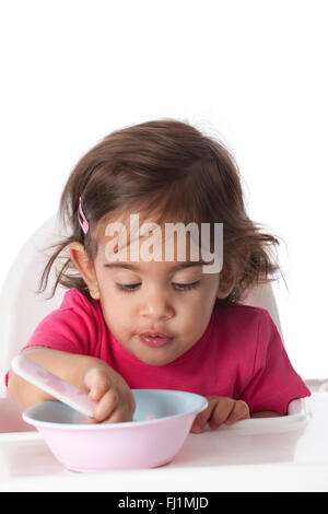 Baby girl is eating by herself on white background - Stock Photo