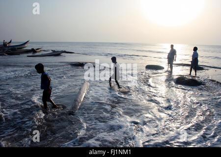 People walk by sunset on the beach in Puri, Orissa, India - Stock Photo
