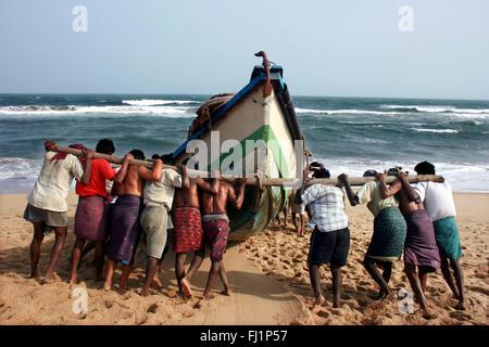 Fishermen pushing boat canoe to the sea before fishing on the beach of Puri, Orissa , India - Stock Photo
