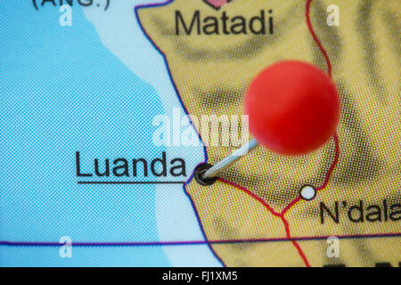 Close-up of a red pushpin in a map of Luanda, Angola. - Stock Photo