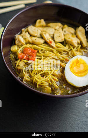 Chicken noodle ramen with egg and ingredients on a dark slate - Stock Photo
