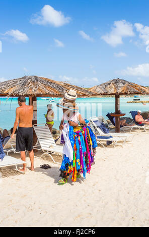 Local woman selling hats and colourful scarves on the beach in Dickenson Bay, north Antigua, Antigua and Barbuda - Stock Photo