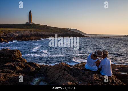 Couple in Punta Herminia gardens,in background Tower of Hercules, Roman lighthouse, Coruña city, Galicia, Spain - Stock Photo