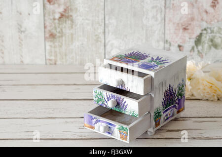 A handmade chest of trinket drawers decoupaged with vintage paperwith pots of Lavender on a rustic wooden background - Stock Photo