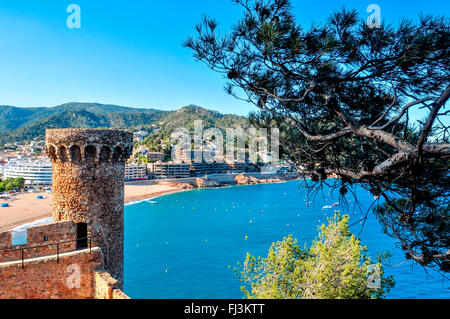 a view of the walls and towers of the Vila Vella, the old town, of Tossa de Mar, Spain with the Platja Gran beach - Stock Photo