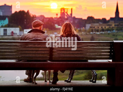 two people sitting on a park bench at lake Phoenix and enjoying the view at sunset, Germany, North Rhine-Westphalia, - Stock Photo