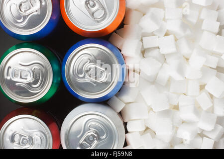 Unhealthy food concept - sugar in carbonated drinks. Sugar cubes as background and canned drink - Stock Photo