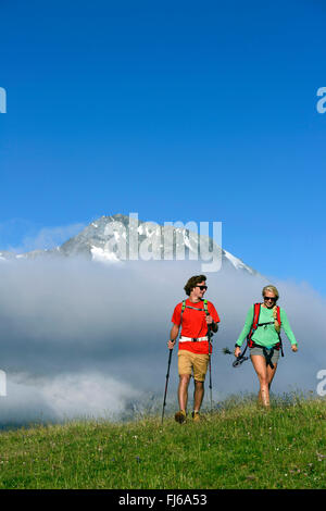 two hikers in a mountain meadow, Mont Pourri in the background, France, Savoie - Stock Photo