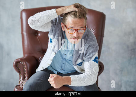 Portrait of a stylish intelligent man with glasses stares into the camera, good view, small unshaven, charismatic, - Stock Photo