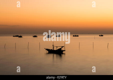 Fishing boats and Sunset in Ha Long Bay, Vietnam - Stock Photo