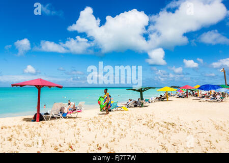 Local woman selling colourful scarves, wraps, sarongs and towels on the beach in Runaway Bay, north Antigua, Antigua - Stock Photo