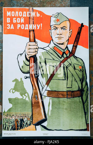 Soviet russian patriotic propaganda poster from World War II with image of soldier transferred rifle. - Stock Photo