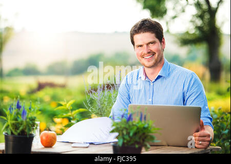 Gardener with notebook, sitting at the table, green nature - Stock Photo