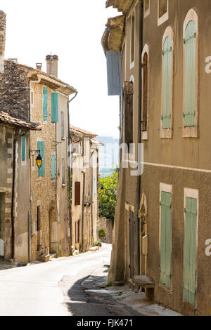 Old stone buildings with painted shutters on a narrow street in the village of Vinsobres, Cotes du Rhone, Provence, - Stock Photo