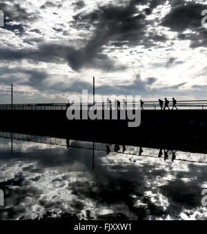 People Walking On Silhouette Bridge Over Calm River Against Cloudy Sky - Stock Photo