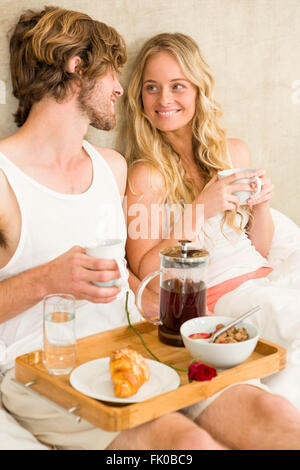 Cute couple having breakfast in bed - Stock Photo