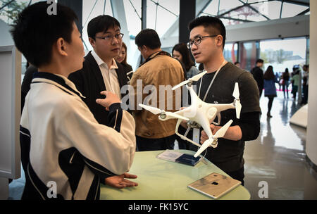 (160305) -- SHENZHEN, March 5, 2016 (Xinhua) -- A staff member (R) introduces Phantom 4 drone developed by major - Stock Photo