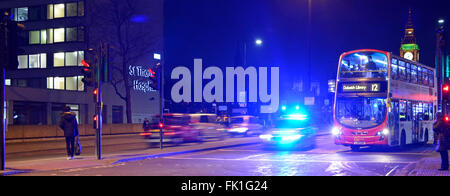 Met police car with blue flashing lights illuminating night sky on Westminster Bridge with red London bus waiting - Stock Photo
