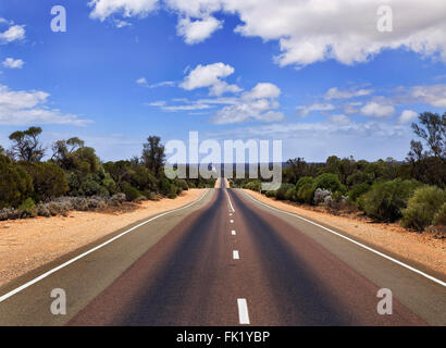 wide empty tarmac sealed Eyre highway in South Australia on a sunny summer day. No cars or traffic in remote areas - Stock Photo