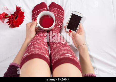 Woman having a cup of tea and texting in bed - Stock Photo
