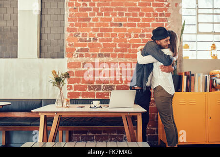 Portrait of man and woman hugging and greeting each other at a coffee shop, couple meeting in a cafe. - Stock Photo