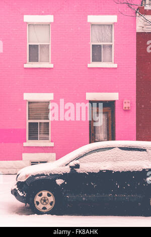 Montreal, CA, 7th March 2016. Black car covered with snow in front of pink traditional house during snow storm - Stock Photo