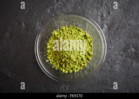 Green matcha powder in a glass bowl on black stone plate - Stock Photo