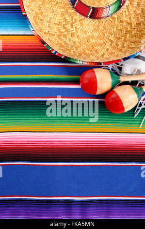 Mexican background with sombrero straw hat, maracas and traditional serape blanket or rug.  Space for copy. - Stock Photo