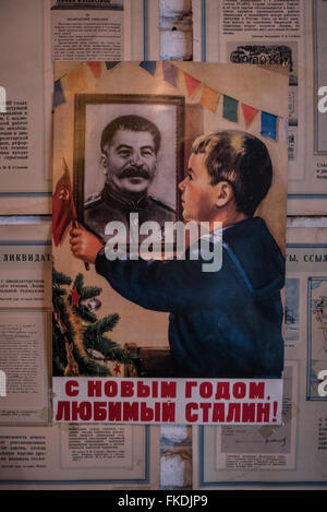 Soviet political poster seen depicting Joseph Stalin and a patriotic young boy seen inside a bar in Tbilisi, Georgia. - Stock Photo