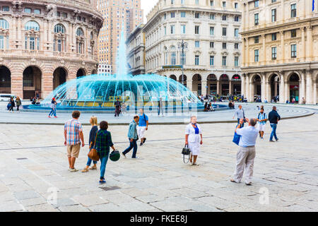 Tourists in place De Ferrari and fountain with blue water (colored to celebrate the boat show) in  Genoa Liguria - Stock Photo