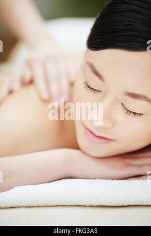Calm female during luxurious procedure of massage - Stock Photo