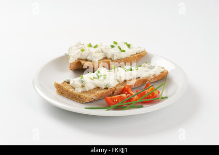 open faced sandwich with chives spread on white plate - Stock Photo