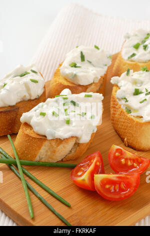 close up of crunchy croutons with chives spread on wooden cutting board - Stock Photo