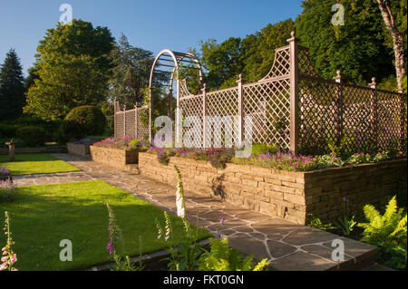 Path, flowering plants, lawn, wall, trellis arch and screen - beautiful sunny, designed, landscaped, garden, Burley - Stock Photo