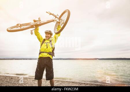 Mature male mountain biker holding up cycle at lakeside - Stock Photo