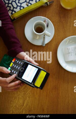 Overhead view of womans hands typing number on credit card machine in restaurant - Stock Photo
