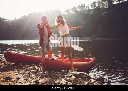 Young man helping woman to step out of canoe. Couple after the canoe ride in the lake. - Stock Photo