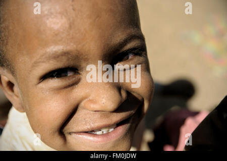 Close-up of a smiling kid at the market of Addi Arkay, Amhara Region, Ethiopia - Stock Photo
