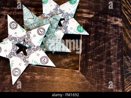 Three different variants of origami cash dollar bills stacked in row in the shape of a stars on old wood brown background - Stock Photo