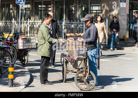 Street vendor selling potatoes to a customer in Beijing, China. - Stock Photo