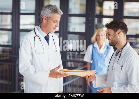 Male doctor giving document to senior - Stock Photo