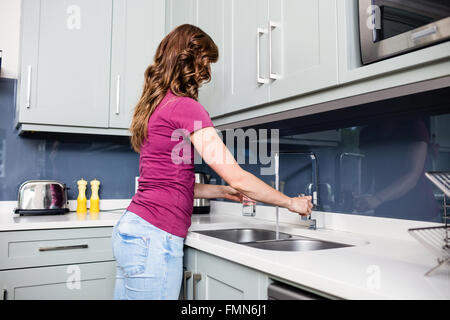 Woman filling water in glass at kitchen counter - Stock Photo
